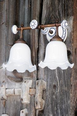 Applique double à tige de laiton patiné, porcelaine blanche décorée et verre opale plissé. Aldo Bernardi.