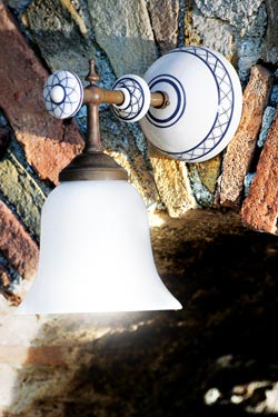 Applique simple à tige de laiton patiné, porcelaine blanche décorée et verre opale lisse. Aldo Bernardi.