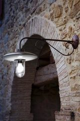 Round outdoor wall light with straight arm in porcelain and brass. Aldo Bernardi.