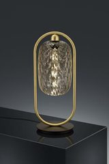 Design golden table lamp and transparent glass. Baulmann Leuchten.