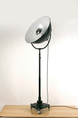 Floor lamp in black metal on wheels, like a projector. Contract&More.