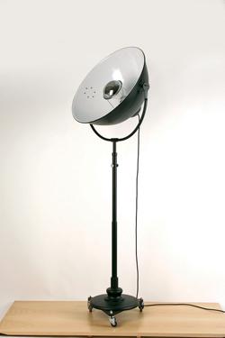 Lampadaire en métal noir sur roulettes, type projecteur . Contract&More.