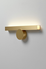 Golden wall lamp, lighting up. CVL Luminaires.