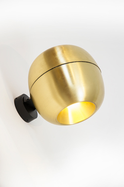 Wall light in the shape of a small golden apple. Dark.