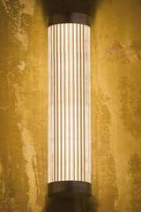 Polished bronze cylindrical and fluted glass wall light. Nautic by Tekna.